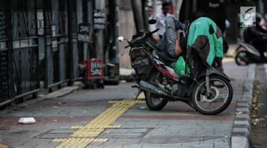 Pengendara motor beristirahat di jalur difabel trotoar di kawasan Sarinah, Jakarta, Rabu (6/1). Kondisi trotoar yang tidak steril ini menyulitkan pejalan kaki, terutama difabel saat melintas. (Liputan6.com/Faizal Fanani)