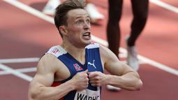 Saking senangnya, ia pun melakukan selebrasi dengan merobek bajunya usai finish dalam pertandingan final lari gawang 400 meter putra pada Olimpiade Tokyo 2020. (Foto: AFP/Guiseppe Cacace)