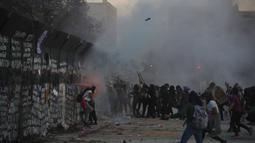 Demonstran menyerang barikade yang melindungi Istana Nasional selama pawai memperingati Hari Perempuan Internasional dan memprotes kekerasan gender di Mexico City, Meksiko, Senin (8/3/2021). Hari Perempuan Internasional diperingati setiap tanggal 8 Maret. (AP Photo/Rebecca Blackwell)