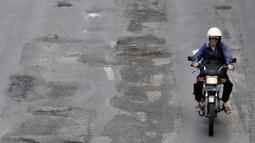 Pengendara motor menghindari jalan berlubang saat melintasi kawasan Gunung Sahari, Jakarta, Selasa (29/1).  Jalan rusak dan berlubang di sepanjang Jalan Gunung Sahari tersebut dapat membahayakan pengendara yang melintas. (Merdeka.com/Iqbal S. Nugroho)