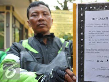 Perwakilan pengemudi ojek memperlihatkan deklarasi damai komunitas ojek pangkalan dengan komunitas ojek online di Polsek Kebun Jeruk, Jakarta (22/9/2015). Acara diselenggarakan unutk menjalin silaturahmi antar pengemudi ojek. (Liputan6.com/Gempur M Surya)