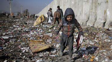 Seorang anak Afghanistan yang kehilangan tempat tinggalnya mencari barang-barang plastik dan lainnya yang dapat digunakan sebagai pengganti kayu bakar, di tempat pembuangan sampah di Kabul, Afghanistan (15/12/2019). (AP Photo/Altaf Qadri)