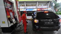 Petugas SPBU sedang mengisi bahan bakar ke salah satu kendaraan roda empat Seiring dengan terus melorotnya harga minyak dunia, Jakarta, Kamis (1/1/2015). (Liputan6.com/Miftahul Hayat)