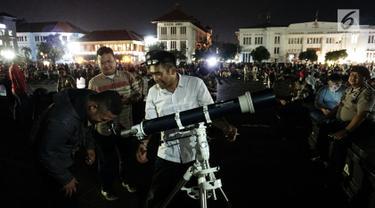 Warga menyaksikan gerhana bulan total lewat teleskop di Kota Tua Jakarta, Rabu (31/1). Selain menyediakan layar lebar, tiga unit teleskop disediakan untuk melihat fenomena super blue blood moon. (Liputan6.com/Arya Manggala)