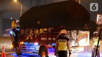 Petugas kepolisian memeriksa sebuah truk saat pemeriksaan dokumen di Pintu Tol keluar Cikarang Barat, kabupaten Bekasi, Jawa Barat, Kamis (6/5/2021) dini hari. Pemeriksaan tersebut terkait larangan mudik lebaran 2021 yang dimulai tanggal 6 hingga 17 Mei. (Liputan6.com/Herman Zakharia)