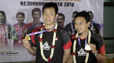 Pasangan ganda putra Indonesia, Mohammad Ahsan/Hendra Setiawan, menunjukan mendali saat konfrensi pers di Bandara Soekarno-Hatta, Tangerang, Selasa (27/8). Ahsan/Hendra meraih gelar pada Kejuaraan Dunia Bulutangkis 2019. (Bola.com/Yoppy Renato)