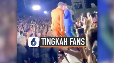 Seorang fans wanita meraba-raba bagian tubuh Nick Jonas ketika konser Jonas Brother sedang berlangsung di Los Angeles, California. Meski telah ditegur petugas, fans tersebut terus melakukannya.