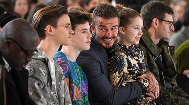 David Beckham bersama anak-anaknya Romeo Beckham, Cruz Beckham dan Harper saat menghadiri peragaan busana Musim Gugur/Musim Dingin 2020 Victoria Beckham dalam acara London Fashion Week di London, (16/2/2020). Beckham tampil dengan setelan jas hitam. (AFP/Daniel Leal-Olivas)