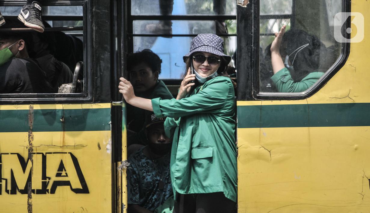 Mahasiswi berada di bus saat mengikuti aksi menolak UU Cipta Kerja di kawasan Patung Kuda, Jakarta, Selasa (20/10/2020). Puluhan mahasiswi turut menghiasi aksi menolak UU Cipta Kerja yang diikuti oleh buruh, mahasiswa, dan pelajar. (merdeka.com/Iqbal S. Nugroho)