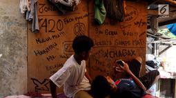 Warga beraktivitas dalam kamarnya yang berada di kawasan padat penduduk, Kapuk, Jakarta, Senin (26/3). Gubernur DKI Jakarta Anies Baswedan mengatakan 50 persen penduduk Jakarta tidak memiliki rumah sendiri. (Liputan6.com/JohanTallo)