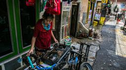 Warga membersihkan barang-barang usai terendam banjir di permukiman kawasan Kampung Melayu, Jakarta, Selasa (9/2/2021). Banjir yang berangsur surut dimanfaatkan warga untuk membersihkan rumah dan barang-barang dari endapan lumpur. (Liputan6.com/Faizal Fanani)