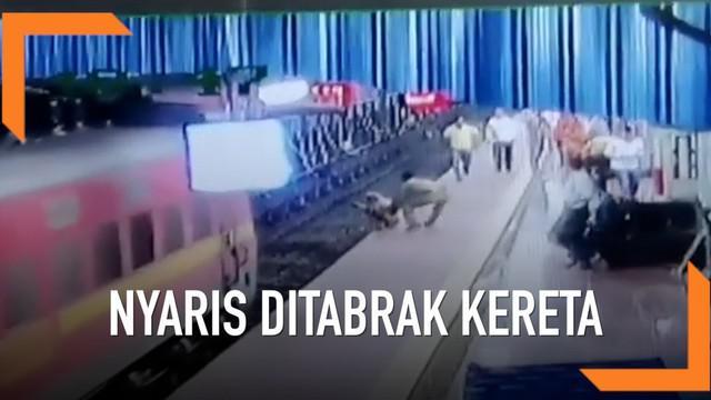 Seorang pria usia 70 tahun penyandang tuna rungu duduk di tepi peron stasiun kereta India. Ia nyaris ditabrak karena tidak menyadari kereta tiba.