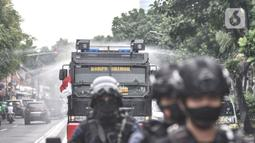 Petugas kepolisian menggunakan kendaraan meriam air saat menyemprotkan cairan disinfektan di Kawasan Petamburan, Jakarta, Minggu (22/11/2020). (merdeka.com/Iqbal S. Nugroho)
