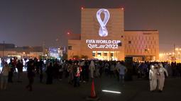 Warga berkumpul menyaksikan proyeksi logo resmi Piala Dunia 2022 yang ditampilkan di sebuah gedung di pasar tradisional Souq Waqif, ibu kota Qatar di Doha, Selasa (3/9/2019).  Lambang itu juga diluncurkan secara serentak di 24 kota besar lainnya di seluruh dunia. (Photo by - / AFP)