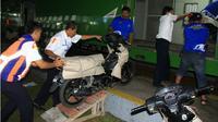 Petugas PT KA Daop 2 Bandung menaikkan sepeda motor ke gerbong kereta program angkutan motor gratis mudik Lebaran 2018, Bandung, Selasa, 22 Mei 2018. (Liputan6.com/Arie Nugraha)