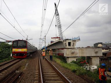 Kereta melintas disamping pembangunan kontruksi jalur DDT di Jakarta, Jumat (13/4). Menhub Budi Karya Sumadi menargetkan penyelesaian pembangunan proyek infrastruktur jalur DDT Manggarai- Cikarang selesai pada 2020. (Liputan6.com/Johan Tallo)