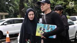 Lyra Virna dan suaminya Fadlan saat tiba di Ditreskrimsus Polda Metro Jaya, Jakarta, Kamis (22/3). Lyra datang untuk memenuhi panggilan terkait statusnya sebagai tersangka kasus dugaan pencemaran nama baik sebuah travel umrah. (Liputan6.com/Faizal Fanani)