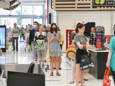 Orang-orang mengantre di supermarket setelah pemerintah negara bagian Australia Selatan mengumumkan penguncian (lockdown) di Adelaide pada Rabu (18/11/2020). Otoritas Australia Selatan memberlakukan lockdown selama enam hari untuk mengendalikan penyebaran virus corona. (Brenton EDWARDS/AFP)