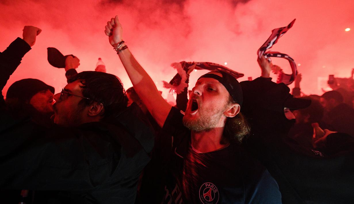 Para suporter Paris Saint-Germain (PSG) merayakan kemenangan PSG atas Borussia Dortmund di depan Stadion Parc des Princes, Paris, Rabu (11/3/2020). Kemenangan tersebut mengantarkan PSG ke perempat final Liga Champions. (AFP/Franck Fife)