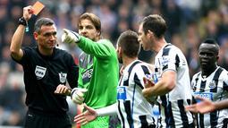 Wasit Andre Marriner memberikan kartu merah Mapou yanga-Mbiwa pada pertandingan Liga Premier Inggris antara Newcastle United vs Liverpool di St James 'Park, Inggris (19/10/2013). (AFP/Ian Macnicol)