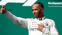 Pembalap Mercedes, Lewis Hamilton berselebrasi setelah berhasil menjuarai GP Hungaria di Sirkuit Hungaroring, Mogyorod, (29/7). Kemenangan Hamilotn menjadi yang kelima sepanjang musim ini. (AP Photo/Laszlo Balogh)