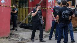 Sejumlah petugas mengecek bar usai penembakan massal di kota Belm, negara bagian utara Par, Brazil (19/5/2019). Sebanyak 11 orang dilaporkan tewas dalam serangan yang dilakukan 7 pria bersenjata tersebut. (Claudio Pinheiro/Agencia Panamazonica/AFP)