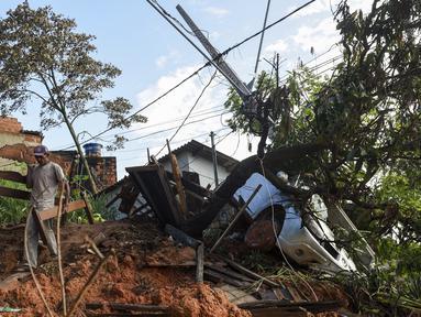 Seorang warga membawa tempat tidur kayu yang dibongkar setelah tanah longsor akibat hujan lebat di Belo Horizonte, Brasil (27/1/2020). Lebih dari 30.000 orang terlantar akibat hujan lebat di Brasil tenggara yang juga menewaskan lebih dari 50 orang. (AP Photo/Gustavo Andrade)