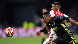 Pemain Ajax Amsterdam, Hakim Ziyech berebut bola dengan pemain Juventus, Alex Sandro pada laga pertama perempat final Liga Champions 2018-2019 di Amsterdam Arena, Rabu (10/4). Juventus harus puas bermain imbang 1-1 di kandang Ajax Amsterdam. (AP/Peter Dejong)