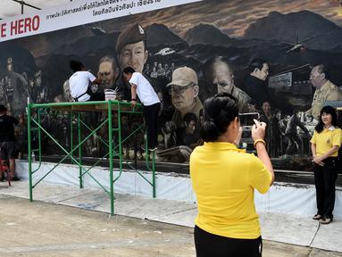 Pengunjung berfoto depan mural raksasa berjudul 'The Heroes' di Chiang Rai, Thailand, 18 Juli 2018. Mural itu untuk menghormati upaya penyelamatan 12 remaja dan pelatih sepak bola yang terperangkap di  gua lebih dari dua minggu. (AFP/Lillian SUWANRUMPHA)