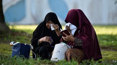 Korban selamat Nurhayati (kanan) berdoa saat memperingati 15 tahun musibah gempa dan tsunami di Kuburan Massal Siron, Aceh, Kamis (26/12/2019). Pada 26 Desember 2004, gempa magnitudo 9,3 memicu gelombang tsunami setinggi 30 meter dan menewaskan sekitar 170 ribu warga Aceh. (CHAIDEER MAHYUDDIN/AFP)