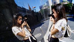 Gista tampaknya memang menggemari fotografi. Saat liburan ia selalu membawa kameranya. Menggunakan baju putih dan celana berwarna hitam, ia tampak sedang memotret dirinya sendiri di sebuah dinding kaca. (Liputan6.com/IG/@gistaputri)