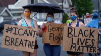 "Sejumlah wanita memegang spanduk saat unjuk rasa atas kematian George Floyd oleh polisi di dekat TKP di Minneapolis, Minnesota, Amerika Serikat, Rabu (27/5/2020). Mayoritas demonstran hadir sambil membawa spanduk bertuliskan ""I Can't Breathe"" dan ""Justice 4 Floyd"". (Kerem Yucel/AFP)"