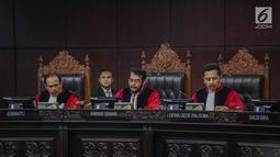 Ketua Majelis Hakim Konstitusi Anwar Usman (tengah) saat membacakan putusan MK di Gedung MK, Jakarta, Kamis (27/6/2019). MK menolak seluruh gugatan hasil Pilpres 2019 yang diajukan Prabowo Subianto-Sandiaga Uno yang disepakati sembilan hakim konstitusi. (Liputan6.com/Faizal Fanani)