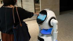 Sebuah robot pemandu membantu pengunjung dalam uji coba yang dilakukan di sebuah bangunan komersial di Tokyo, Jepang (14/9/2020). Robot-robot ini diharapkan dapat membantu masyarakat mengurangi risiko terjangkit COVID-19. (Xinhua/Pemerintah Kota Metropolitan Tokyo)