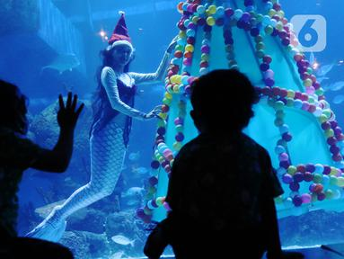 Anak-anak menyaksikan penyelam berkostum putri duyung di dalam air yang dihiasi pohon natal di Jakarta Aquarium dan Safari, Mal Neo Soho, Grogol, Jakarta, Kamias (24/12/2020). Pertunjukan tersebut untuk mengisi libur Natal dan Tahun Baru 2021. (Liputan6.com/Angga Yuniar)