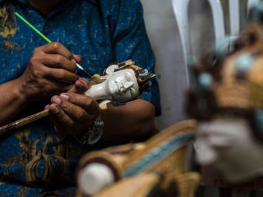 Seorang pengrajin mewarnai wayang kayu khas Sunda atau wayang golek di galeri kerajinan tangan Cupumanik di Bandung, Jawa Barat, 17 Februari 2020. Galeri kerajinan tangan Cupumanik memproduksi berbagai wayang golek untuk dijual sebagai cendera mata bagi wisatawan lokal maupun asing. (Xinhua/Septianj