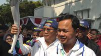 Menkominfo Rudiantra seusai menerima obor dari Wali Kota Bogor Bima Arya saat kirab obor Asian Games 2018 di Kota Bogor, Jawa Barat, Selasa (14/8). Rudiantara menjadi orang pertama pembawa obor dengan berlari sepanjang 500 meter. (Merdeka.com/Arie Basuki)