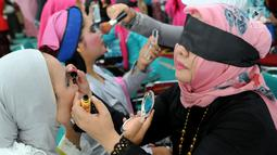 Peserta merias wajah dengan mata tertutup di Kantor Balai Kota Tangerang Selatan, Banten, Jumat (27/4). Perlombaan ini dalam rangka memperingati Hari Kartini. (Merdeka.com/Arie Basuki)