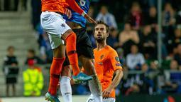 Penyerang Belanda, Donyell Malen (kiri) dan gelandang Estonia, Martin Miller berebut bola saat bertanding dalam kualifikasi Grup C Euro 2020, di Tallinn, Estonia, Senin (9/9/2019). Belanda mengalahkan Estonia dengan skor 4-0. (Raigo Pajula/AFP)