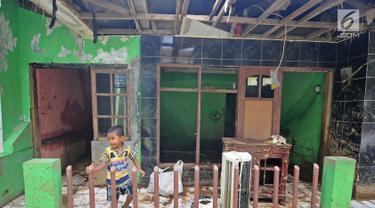Seorang anak bermain di rumah yang rusak akibat terjangan banjir di kawasan  Balekambang, Kramatjati, Jakarta Timur, Selasa (30/4/2019). Sejumlah rumah warga di RT 005/RW 005 Balekambang rusak diterjang banjir yang terjadi pada 27 April 2019 lalu. (Liputan6.com/Herman Zakharia)