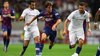 Gelandang Barcelona, Riqui Puig, berusaha melewati striker Chelsea, Pedro, pada laga pramusim di Stadion Saitama, Jepang, Selasa (23/7). Chelsea menang 2-0 atas Barcelona. (AFP/Charly Triballeau)