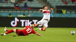 Pemain Swiss Granit Xhaka (kiri) berebut bola dengan pemain Turki Cengiz Under pada pertandingan Grup A Euro 2020 di Stadion Olimpiade Baku, Baku, Azerbaijan, Minggu (20/6/2021). Swiss menang 3-1. (Ozan Kose/Pool via AP)