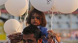 Pria dan anaknya memegang balon saat upacara untuk memperingati peristiwa ledakan pelabuhan 4 Agustus di Beirut, Lebanon, 4 Oktober 2020. Dua ledakan yang mengguncang Pelabuhan Beirut menghancurkan sebagian kota dan menewaskan sekitar 190 orang serta melukai 6.000 lainnya. (Xinhua/Bilal Jawich)