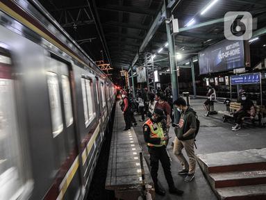 Penumpang menunggu kedatangan KRL di Stasiun Manggarai, Jakarta, Selasa (12/1/2021). Selama PSBB di DKI mulai 11-25 Januari, PT Kereta Commuter Indonesia (KCI) memangkas jadwal operasional KRL menjadi pukul 04.00 WIB hingga 22.00 WIB guna menekan penularan Covid-19. (merdeka.com/Iqbal Nugroho)