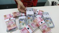 Teller menunjukkan mata uang rupiah dan dolar di Bank Mandiri, Jakarta, Kamis (10/1). Hingga hari ini, US$ 1 dibanderol Rp 14.020. Rupiah menguat 0,71% dibandingkan posisi penutupan perdagangan hari sebelumnya. (Liputan6.com/Angga Yuniar)