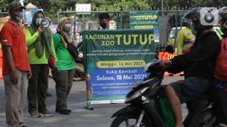 Petugas Satpol PP memberitahu warga terkait penutupan kawasan Kebun Binatang Ragunan, Jakarta, Minggu (16/5/2021). Sejumlah kawasan wisata di DKI Jakarta ditutup sementara untuk umum hingga 18 Mei 2021 untuk pemberlakukan penguatan protokol kesehatan COVID-19. (Liputan6.com/Helmi Fithriansyah)