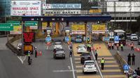 Polisi dan petugas Dishub berjaga di depan Gerbang Tol Bekasi Barat 1, Bekasi, Jawa Barat, Senin (12/3). Peraturan ganjil genap ini berlaku mulai hari ini, Senin (12/3) pukul 06.00-09.00. (Liputan6.com/Arya Manggala)