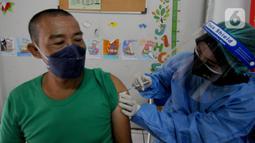 Seorang guru menerima vaksin COVID-19 di dalam ruang kelas SDIT Al Muhajirin, Depok, Selasa (18/5/2021). Sebanyak 2.000 guru di wilayah Depok divaksinasi dalam rangka persiapan kegiatan pembelajaran tatap muka pada tahun ajaran baru Juli mendatang. (merdeka.com/Arie Basuki)