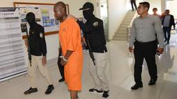 Abdul Rachman Azman asal Tanzania dikawal petugas sebelum konferensi pers di Kantor Pelayanan Bea Cukai Bandara Ngurah Rai, Bali, Selasa (12/2). Abdul menyelundupkan sabu dengan modus menelan 99 butir yang diperkirakan mencapai 1 kg. (Sonny TUMBELAKA/AFP)