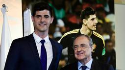 Kiper asal Belgia Thibaut Courtois menunjukkan jersey klub barunya Real Madrid saat berpose dengan presiden Real Madrid, Florentino Perez  di stadion Santiago Bernabeu (9/8). Courtois dikontrak Madrid selama 6 tahun. (AFP Photo/Javier Soriano)